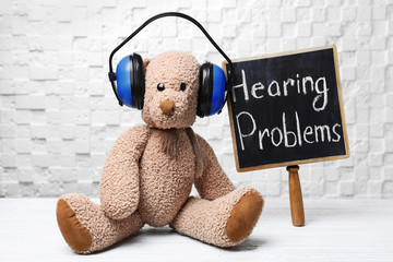 Toy bear, headphones and chalkboard with words HEARING PROBLEMS on table