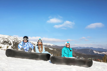 Group of snowboarders on ski piste at snowy resort. Winter vacation