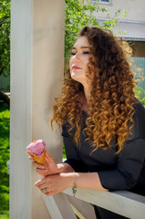stylish woman with chic curly hair eating ice cream in the courtyard of a country house.