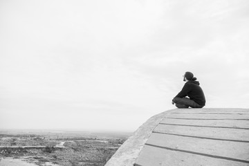 Side view unidentified young man in casual clothes and glasses sits on the high rock and looks at beautiful desert