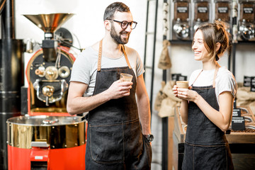 Portrait of a couple of baristas in uniform standing together in the coffee shop with coffee roasting machine on the background