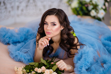 beautiful girl with dark hair with flowers in her hands in a blue dress