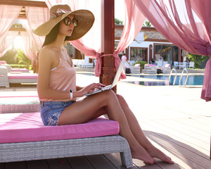 Work and travel. Incredibly sexy sits with a laptop near the pool. Find a tour. The blogger. Vlog. Communication. Recreation. Resort. Delicate shiny skin. Brunette.