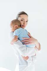 beautiful female pediatrician carrying little baby isolated on white
