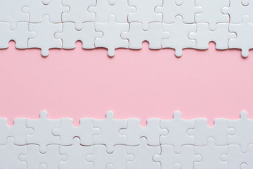 Wall Mural - White details of puzzle on pink background and place for inscription