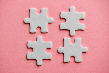 Wall Mural - four white details of puzzle on pink background