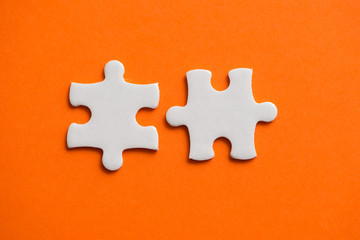 Wall Mural - Two white details of puzzle on orange background