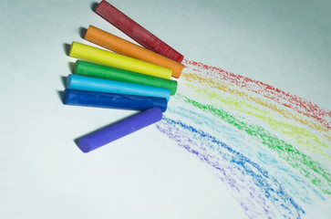crayons to draw and color lines on a white sheet of paper