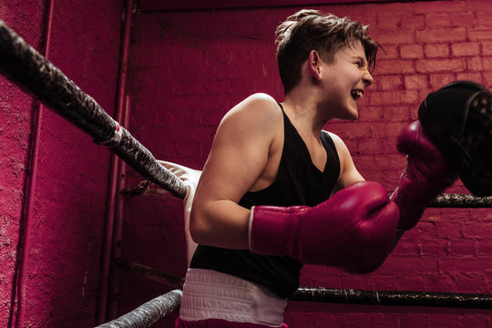 Young male boxer training on the ring for a fight