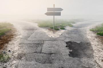 Wegweiser an Weggabelung im Nebel