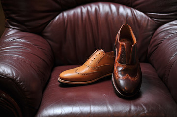leather handmade shoes on a leather sofa with a dark color
