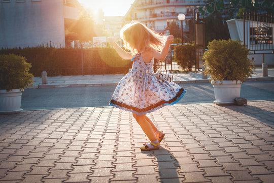 Little girl spinning around him in the street