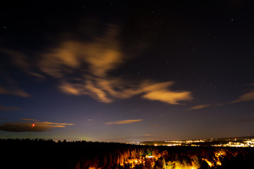 A city and a forest under the sky with stars. Sweden
