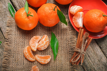 Mandarin oranges with leaves on rustic wood background. Citrus just from the tree.Organic veg food.Winter fruits.
