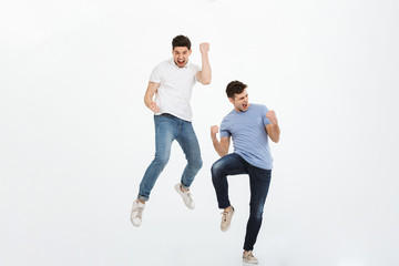 Full length portrait of two happy young men jumping