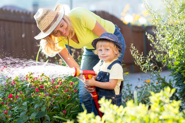 Woman and her little son watering flowers in garden