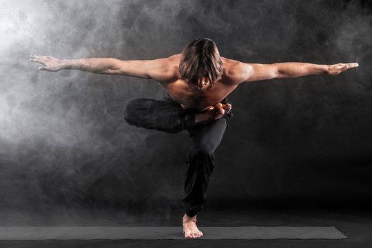 Acroyoga. Young man practicing acro yoga on mat.