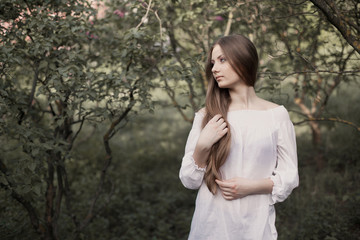 Beautiful young woman in city park in spring. Attractive young woman posing outdoor. Beauty, fashion concept.