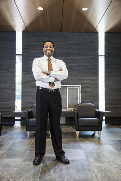 Black businessman in the lobby of a large office building.