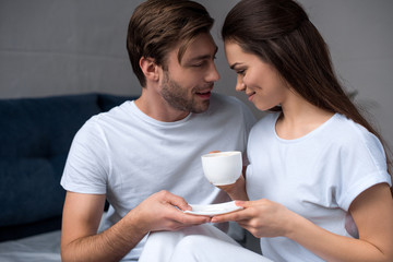 Beautiful young couple drinking coffee in bed
