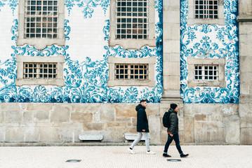 Cheerful men walking at colorful building