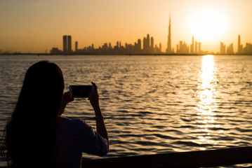 Woman taking photo of Dubai at sunset
