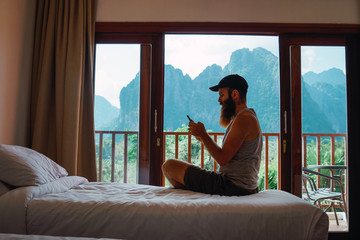 Man with smartphone on bed