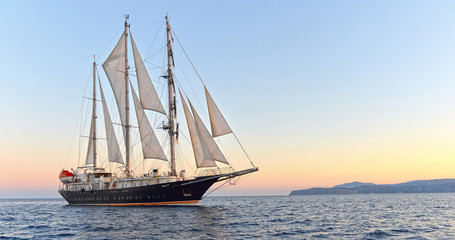Sailing ship and beautiful sunset in the sea.  Yachting. Sailing