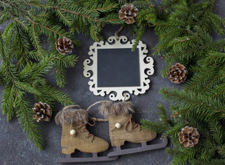 on a festive background a plaque for notes, cones, pine branches and skates