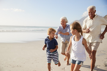 Grandparents Running Along Beach With Grandchildren On Summer Vacation