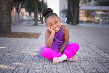 Little girl wearing tutu and sitting on sidewalk