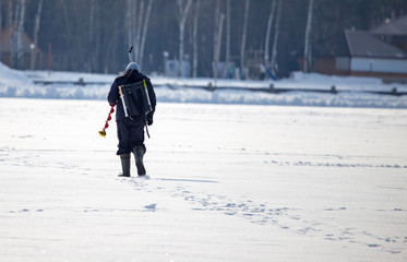 A man catches fish on ice in winter