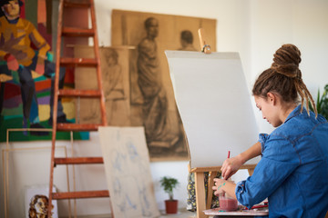 Girl prepating to paint on easel in atelier.