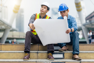 Engineer men meeting outdoor using blueprint