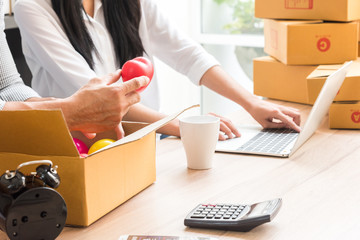 professional young online shopping company team of two co worker with box of products in office background and face to camera. Businessmen hold hearts in their hands for being in the box.