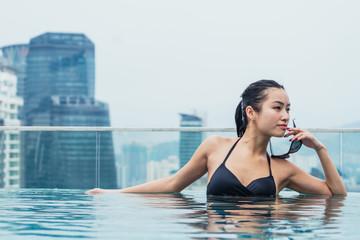 Asian woman relaxing in pool