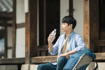 A young man traveling to Korea is taking a rest with a water bottle.