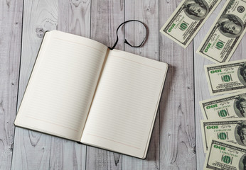 Notepad, pen and money on a light wooden background