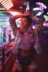 Woman wearing sparkling jacket on the city street with neon lights