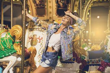 Stylish woman wearing sparkling jacket on the carousel