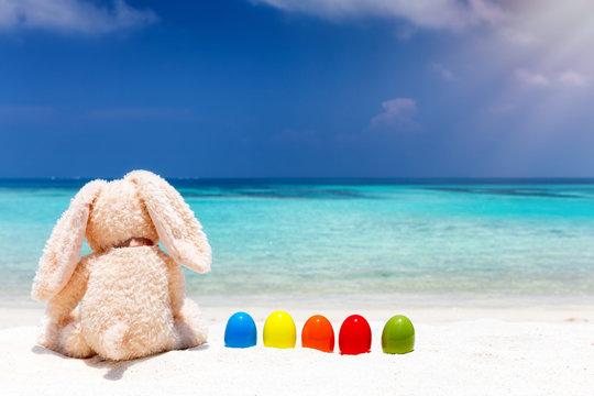 Osterhase mit bunten Ostereiern am Strand