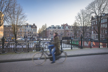 Street life scene in Amsterdam, a bridge with bicycles parked on the bridge rail a cyclist in motion biking over the bridge and typical Dutch canal houses, Amsterdam, The Netherlands