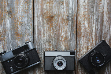 Old photo cameras on old wooden texture. Vintage film cameras on background. Retro and antique photography.