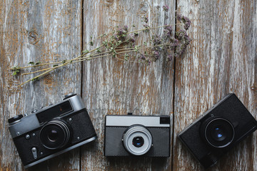 Old photo cameras on old wooden texture. Vintage film cameras with dry flowers on background. Retro and antique photography.
