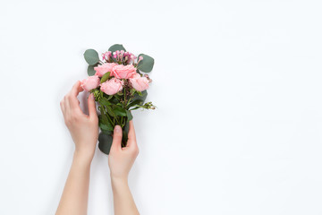 Top view of floral composition of beautiful pink rose flower bouquet in girls hand on white background, flat lay, copyspace