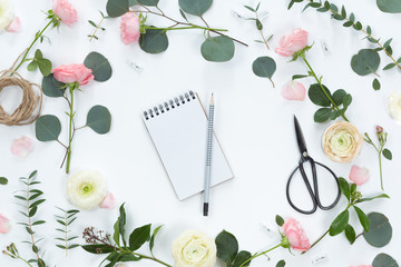 Festive composotion with flowers, notebook, gifts, scissors, ribbons, leaves on a white background, top view and flat lay, floral frame