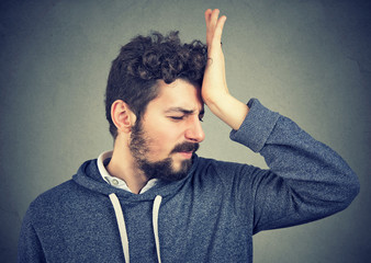 silly regretful young man, slapping hand on head having a duh moment