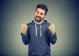 successful student man winning, fists pumped celebrating success