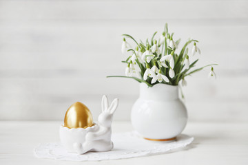 Close-up of beautiful spring decoration with white bouquet of snowdrops flowers and Easter bunny with golden egg