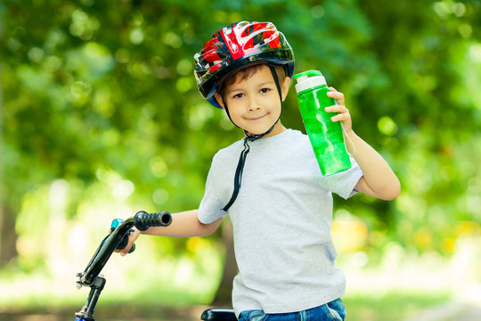 Little boy drinking water by the bike. Happy smiling child in helmet riding a cycling.
